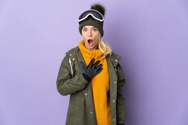 보라색 배경에 격리된 스노보드 안경을 쓴 러시아 스키어 소녀는 오른쪽을 보고 놀라고 충격을 받았습니다.