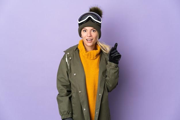 指を上に向けるアイデアを考えて紫色の背景に分離されたスノーボードグラスを持つスキーヤーロシアの女の子