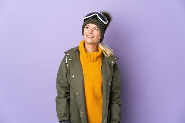 見上げながらアイデアを考えて紫色の背景に分離されたスノーボードグラスを持つスキーヤーロシアの女の子