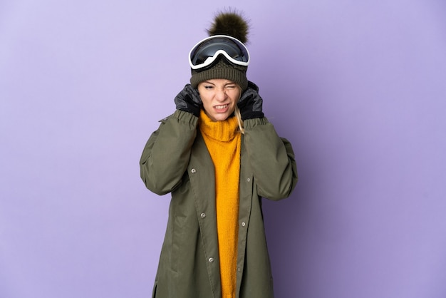 欲求不満と耳を覆う紫色に分離されたスノーボードグラスを持つスキーヤーロシアの女の子
