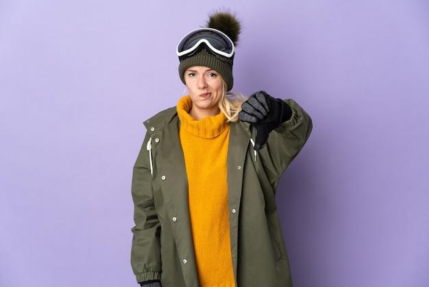 否定的な表現で親指を下に示す紫色に分離されたスノーボードグラスを持つスキーヤーロシアの女の子