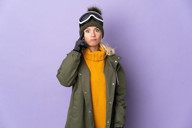 アイデアを考えて紫に分離されたスノーボードグラスを持つスキーヤーロシアの女の子