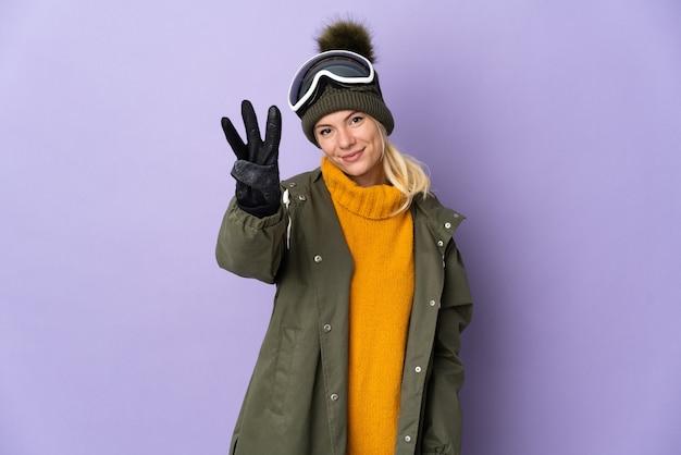 행복 하 고 손가락으로 세 세 보라색 벽에 고립 된 스노우 보드 안경 스키 러시아 소녀