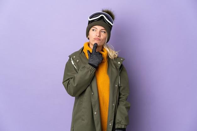 Русская девушка-лыжница в очках для сноуборда изолирована на фиолетовой стене, сомневаясь, глядя вверх