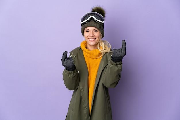 Русская девушка лыжника в очках для сноуборда изолирована на фиолетовой стене, делая денежный жест