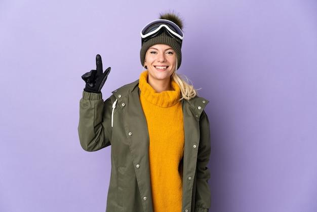 Русская девушка-лыжница в очках для сноубординга изолирована на фиолетовой стене, указывая на отличную идею