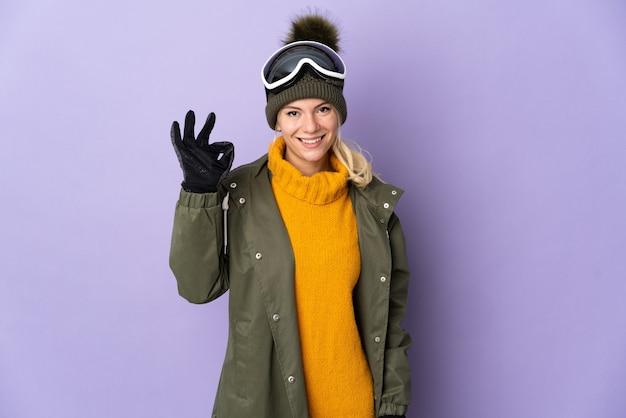 Русская девушка-лыжница в очках для сноуборда изолирована на фиолетовой стене, показывая пальцами знак ок