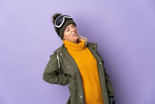 Русская девушка-лыжница в очках для сноуборда изолирована на фиолетовой стене и страдает от боли в спине из-за того, что приложила усилие