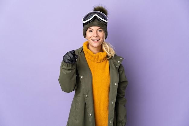 Русская девушка лыжника в очках для сноуборда изолирована на фиолетовой стене удивлена и указывает вперед