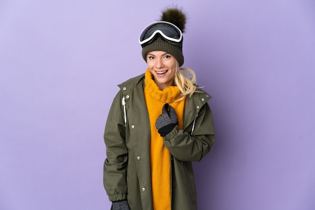 驚きの表情で紫に分離されたスノーボードグラスを持つスキーヤーロシアの女の子