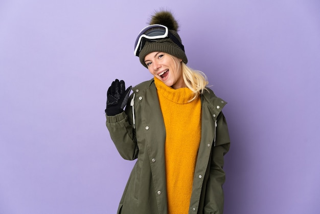 Skier russian girl with snowboarding glasses isolated on purple background saluting with hand with happy expression