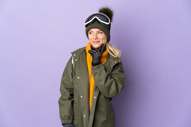 Skier russian girl with snowboarding glasses isolated on purple background thinking an idea while looking up