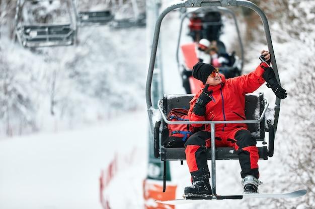 스키 리프트에 앉아 있는 스키어는 화창한 날 높은 산에서 전화로 셀카를 찍습니다. 겨울 스포츠 및 레크리에이션, 레저 야외 활동.