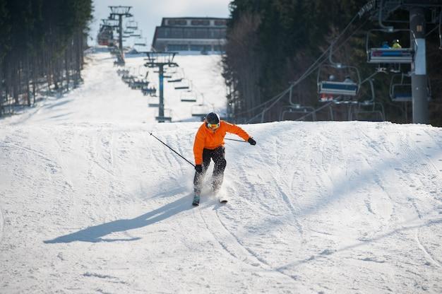 Skier skiing downhill after jumping at ski resort against ski-lift and snow slope