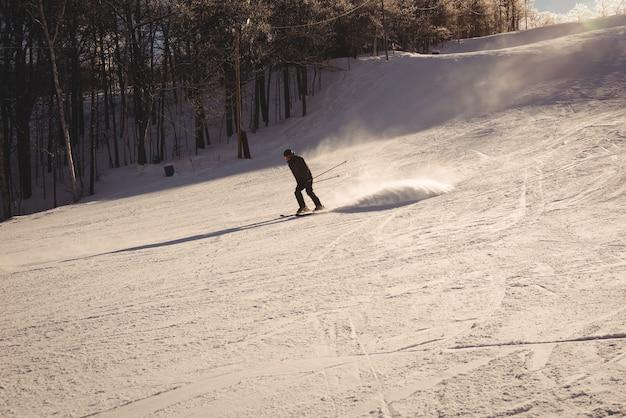 山の斜面でスキーをするスキーヤー