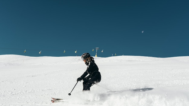 Skier skiing on a snowy surface wearing skiing outfit and helmet