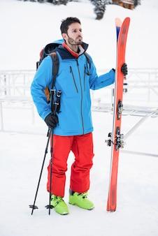雪に覆われた山々の上に立ってスキーヤー