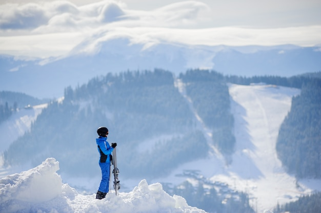Skier standing on top of the mountain and enjoying the view on beautiful winter mountains on a sunny day