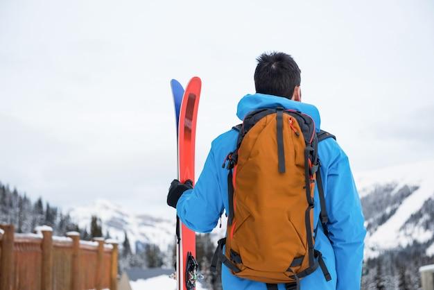 雪に覆われた山々でスキーと立っているスキーヤー
