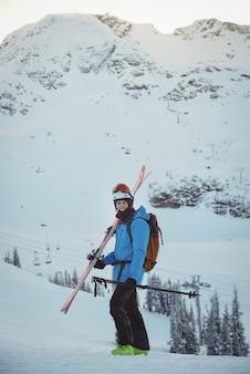 雪景色にスキーで立っているスキーヤー
