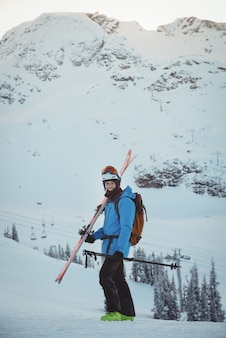 Skier standing with ski on snowy landscape