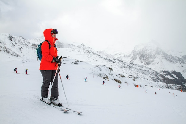 The skier stands on the slope before the descent and watches the training of skiers