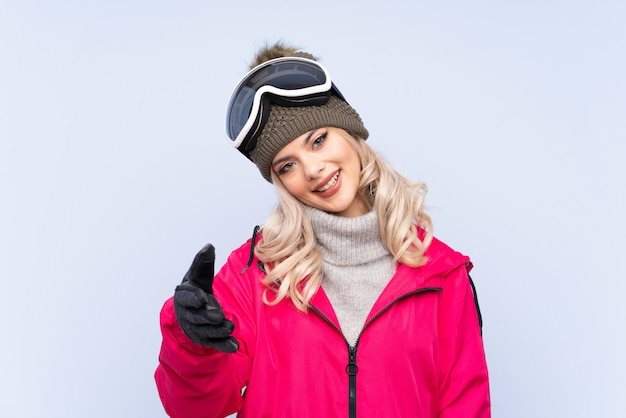 Skier teenager girl with snowboarding glasses over isolated blue background handshaking after good deal