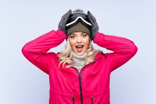 Skier teenager girl with snowboarding glasses over isolated blue  with surprise facial expression