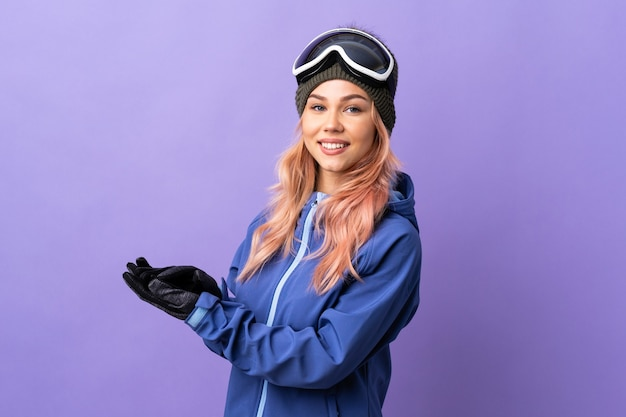 Skier teenager girl with snowboarding glasses over isolated purple wall applauding