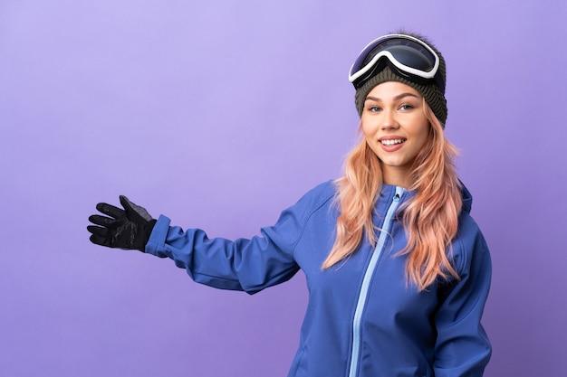 Лыжник-подросток в очках для сноубординга на изолированном фиолетовом фоне, протягивая руки в сторону, чтобы пригласить приехать