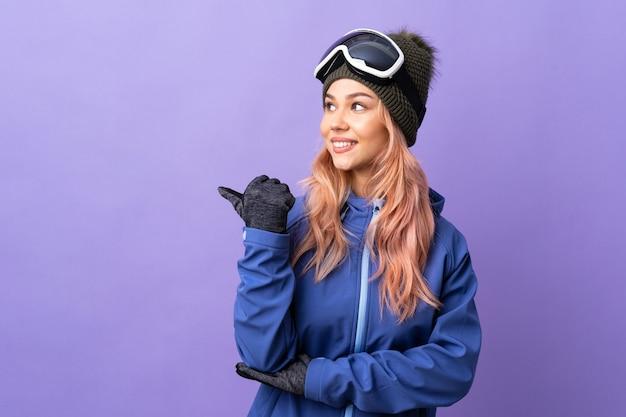 제품을 제시하는 측면을 가리키는 격리 된 보라색 배경 위에 스노우 보드 안경 스키 십 대 소녀