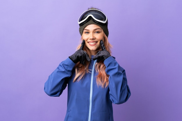 행복하고 즐거운 표정으로 웃는 격리 된 보라색 배경 위에 스노우 보드 안경 스키 십 대 소녀