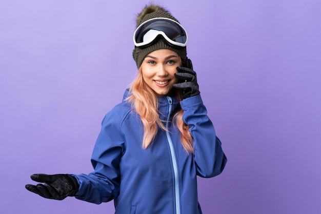 Девушка-подросток лыжника в очках для сноуборда над изолированным фиолетовым разговаривает с кем-то по мобильному телефону