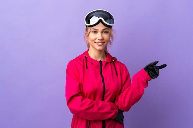 측면에 고립 된 보라색 가리키는 손가락을 통해 스노우 보드 안경 스키 십 대 소녀