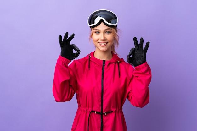 두 손으로 확인 표시를 보여주는 고립 된 보라색 위에 스노우 보드 안경 스키 십 대 소녀