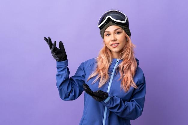 Лыжница-подросток в очках для сноуборда над изолированной фиолетовой стеной протягивает руки в сторону, приглашая приехать