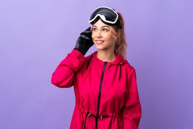 Лыжник-подросток в очках для сноуборда над изолированной фиолетовой стеной, разговаривает по мобильному телефону