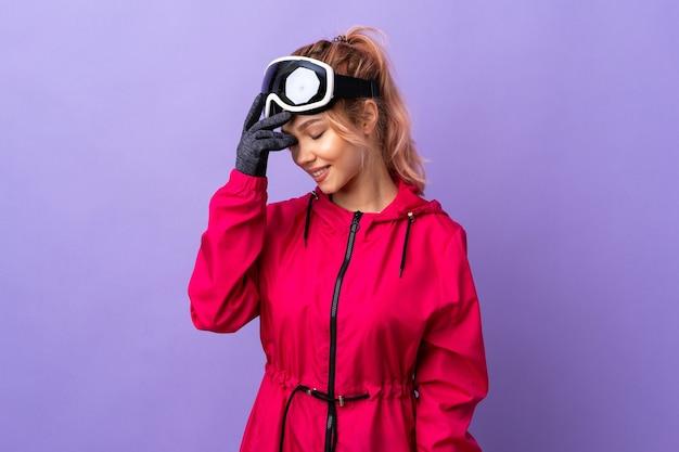 笑っている孤立した紫色の壁の上のスノーボードメガネとスキーヤーのティーンエイジャーの女の子