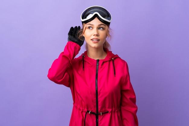 耳に手を置くことによって何かを聞いている孤立した紫色の壁の上にスノーボードグラスを持つスキーヤーのティーンエイジャーの女の子
