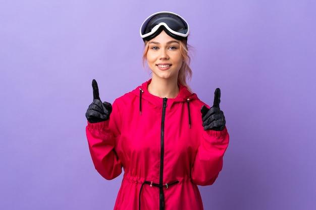 Лыжница-подросток в очках для сноубординга над изолированной фиолетовой стеной, указывая вверх на отличную идею
