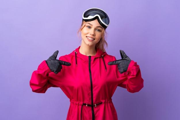Лыжница-подросток в очках для сноуборда над изолированной фиолетовой стеной, гордая и самодовольная