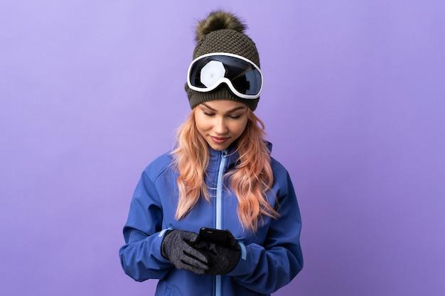 Девушка-подросток лыжника в очках для сноуборда над изолированной фиолетовой стеной отправляет сообщение с мобильного телефона
