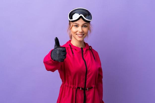 何か良いことが起こったので、親指を立てて孤立した紫色の壁にスノーボードグラスを持ったスキーヤーのティーンエイジャーの女の子