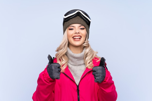 Skier teenager woman with snowboarding glasses giving a thumbs up gesture