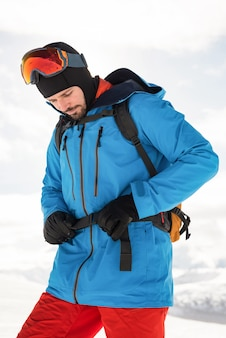 Skier tightening his backpack belt