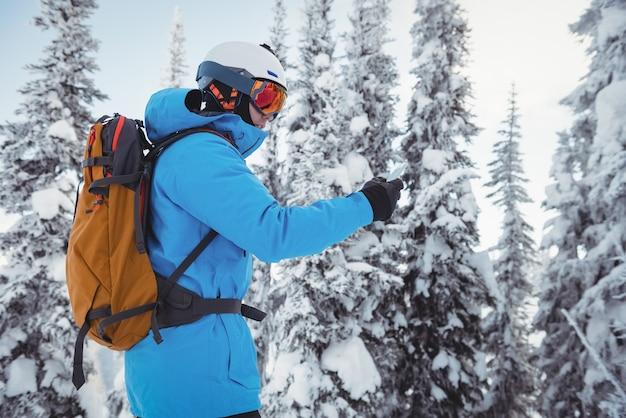 Лыжник с помощью мобильного телефона на заснеженных горах