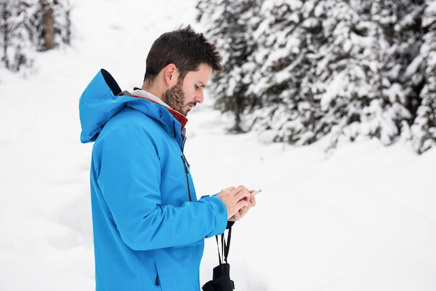 Skier using mobile phone on the snowy mountains