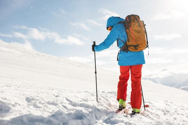 Лыжник гуляет по склону с лыжами