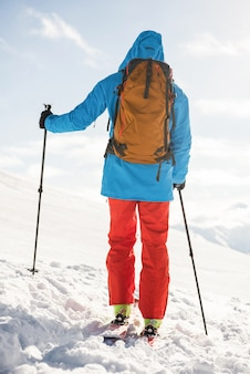 Skier walking on the slope with ski