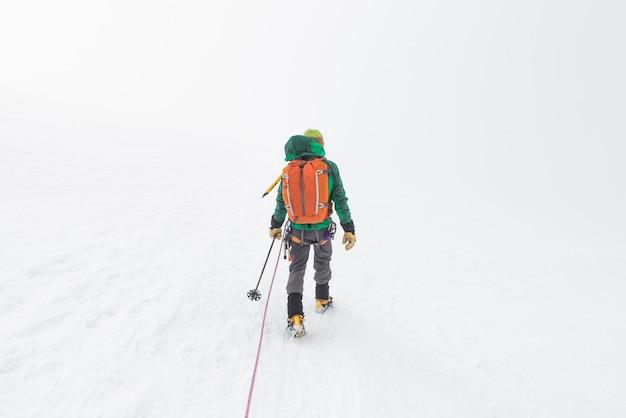 Лыжник идет вверх по крутому снежному склону в горах
